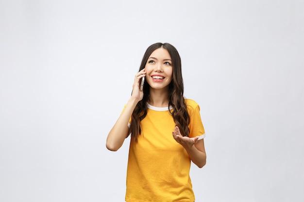Schöne junge asiatische frau, die handy und lächeln spricht