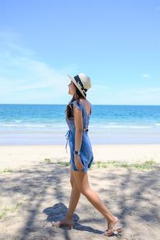 Schöne junge asiatische frau, die hut trägt, der auf dem strand im tropischen meer geht.