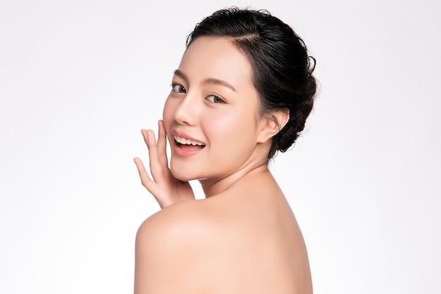 Schöne junge asiatische frau, die ihr sauberes gesicht mit frischer gesunder haut berührt, isoliert, schönheitskosmetik- und gesichtsbehandlungskonzept