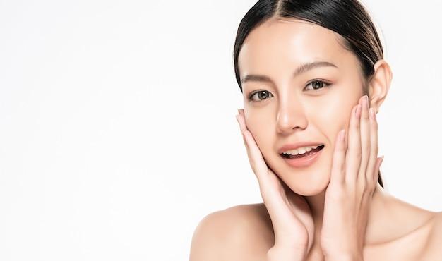 Schöne junge asiatische frau, die ihr sauberes gesicht mit frischer gesunder haut berührt, lokalisiert auf weiß