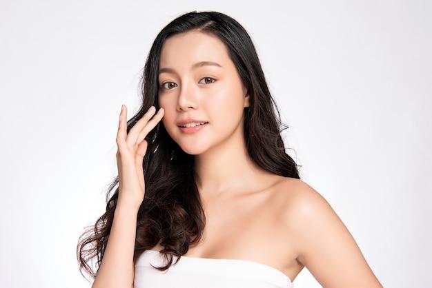 Schöne junge asiatische frau, die ihr sauberes gesicht mit frischer gesunder haut berührt, lokalisiert auf weißer wand, schönheitskosmetik- und gesichtsbehandlungskonzept,
