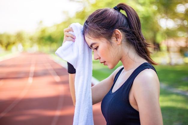 Schöne junge asiatische frau, die ihren schweiß nach ihrer morgenübung an einer laufbahn abwischt