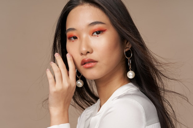 Schöne junge asiatische frau, die in den stilvollen kleidern aufwirft