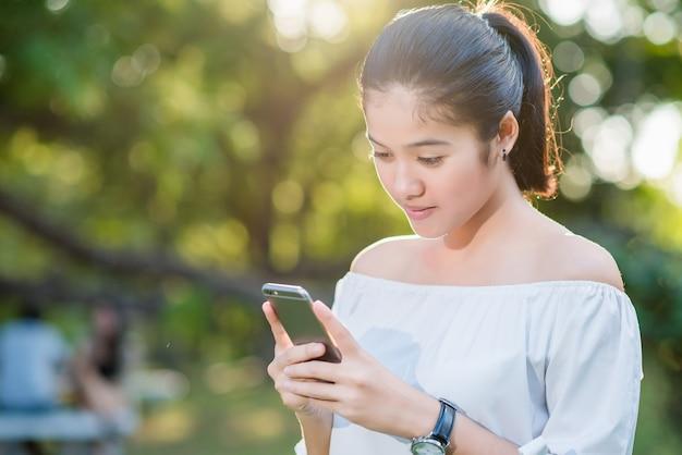 Schöne junge asiatische frau, die lächelt, während sie ihr smartphone in einem garten liest.