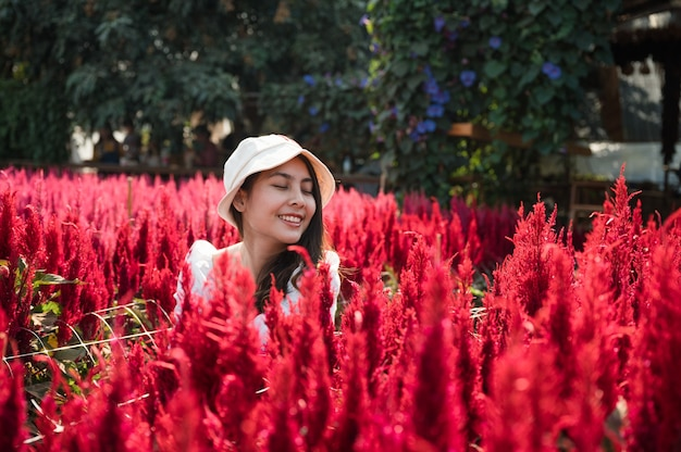 Schöne junge asiatische frau, die mit dem genießen im roten blumengarten des hahnenkamms sitzt