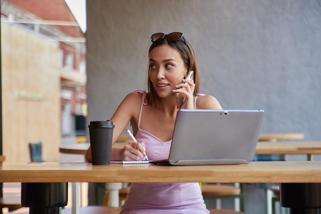Schöne junge asiatische frau, die mit laptop im café sitzt und mit dem smartphone anruft
