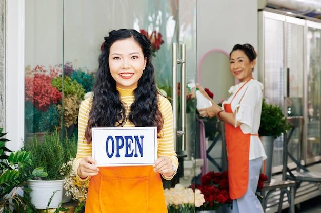 Schöne junge asiatische frau, die mit offenem seufzer im blumenladen steht, ihr mitarbeiter, der blumen mit frischem wasser besprüht