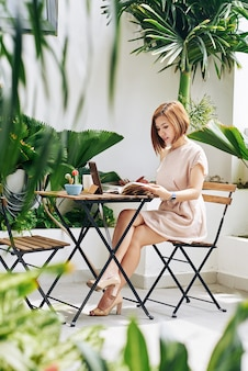 Schöne junge asiatische frau, die morgen im café trinkt und planer mit ideen füllt