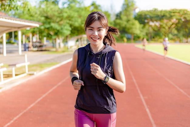 Schöne junge asiatische frau, die morgens an einer laufbahn trainiert