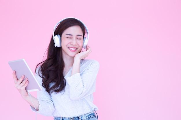 Schöne junge asiatische frau, die musik mit kopfhörern in wiedergabelisten-liedanwendung auf tablett hört