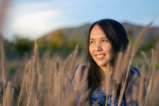 Schöne junge asiatische frau, die natur auf graswiese am sonnenaufgang genießt