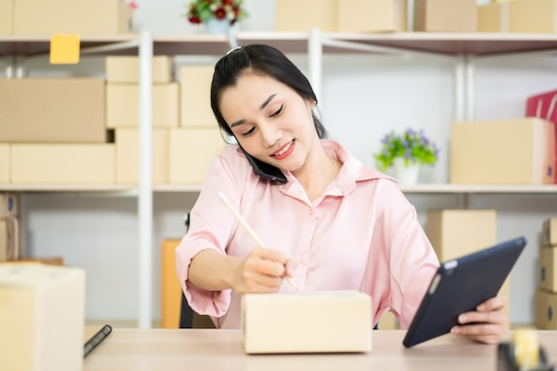 Schöne junge asiatische frau, die online produkte verkauft. recht asiatische mädchenschreibens-postadresse auf einem papierpaketkasten.