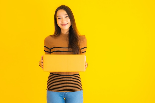 Schöne junge asiatische frau, die pappkarton in ihrer hand auf gelber wand hält
