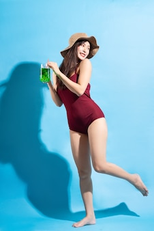 Schöne junge asiatische frau, die roten einteiligen badeanzug trägt und grünen saft trinkt und aufwirft