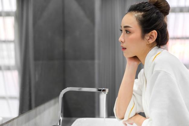 Schöne junge asiatische frau, die sauberes gesicht mit wasser wäscht und vor dem spiegel im badezimmer lächelt. schönheit und spa. perfekte frische haut