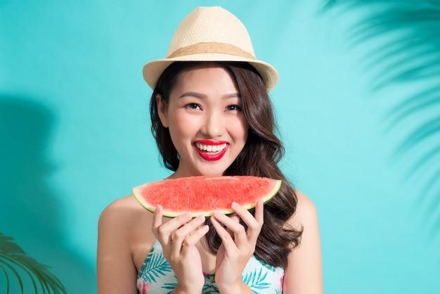 Schöne junge asiatische frau, die scheibe wassermelone hält und lächelt