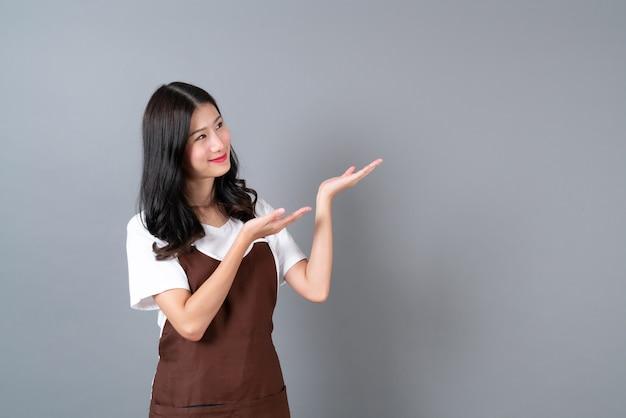 Schöne junge asiatische frau, die schürze mit glücklichem und lächelndem gesicht auf grau mit kopienraum trägt