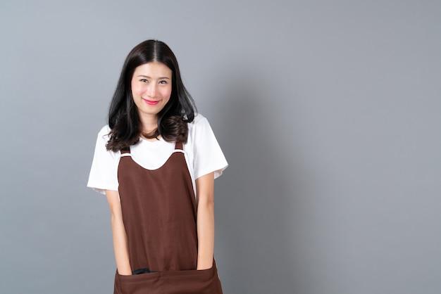 Schöne junge asiatische frau, die schürze mit glücklichem und lächelndem gesicht auf grau trägt