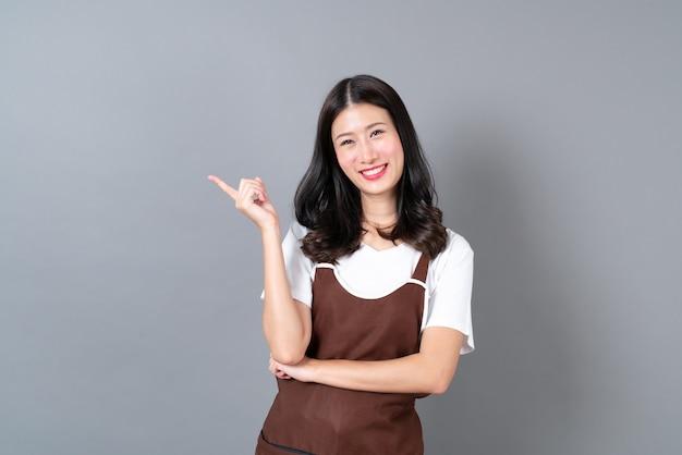 Schöne junge asiatische frau, die schürze mit glücklichem und lächelndem gesicht trägt