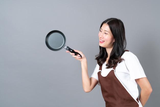 Schöne junge asiatische frau, die schürze mit hand hält, die schwarze pfanne auf grau hält