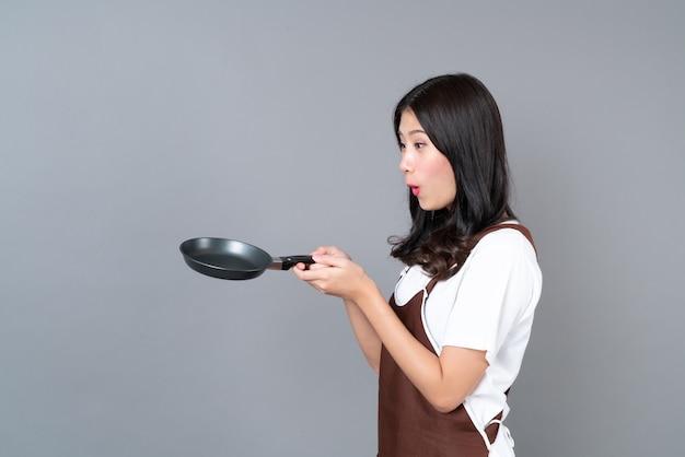 Schöne junge asiatische frau, die schürze mit hand hält, die schwarze pfanne auf grauem hintergrund hält