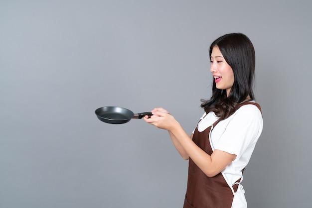 Schöne junge asiatische frau, die schürze mit hand hält, die schwarze pfanne hält