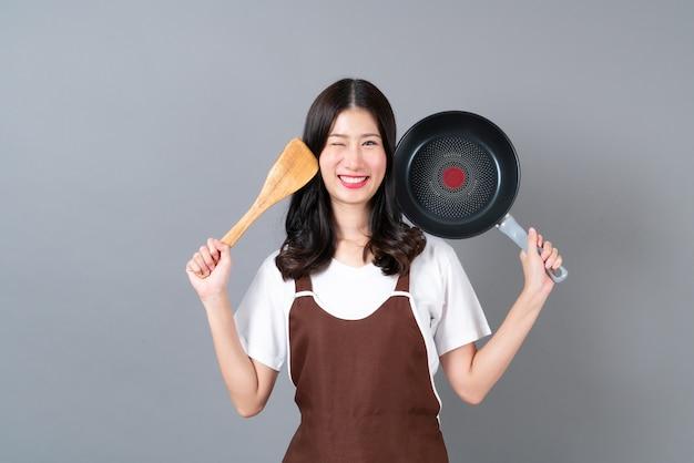 Schöne junge asiatische frau, die schürze mit hand hält, die schwarze pfanne und hölzernen spatel auf grau hält
