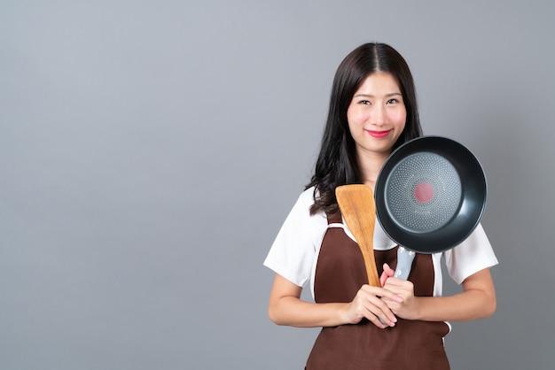 Schöne junge asiatische frau, die schürze mit hand hält, die schwarze pfanne und hölzernen spatel auf grauem hintergrund hält