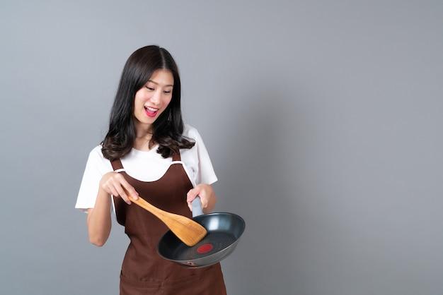 Schöne junge asiatische frau, die schürze mit hand hält, die schwarze pfanne und hölzernen spatel hält