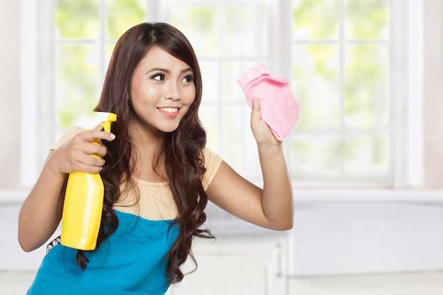 Schöne junge asiatische frau, die sprühgerät und reinigung hält