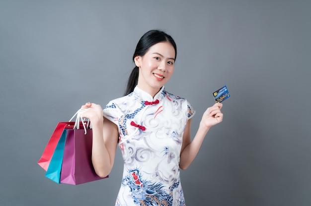 Schöne junge asiatische frau, die traditionelle chinesische kleidung mit einkaufstasche und kreditkarte auf grau trägt