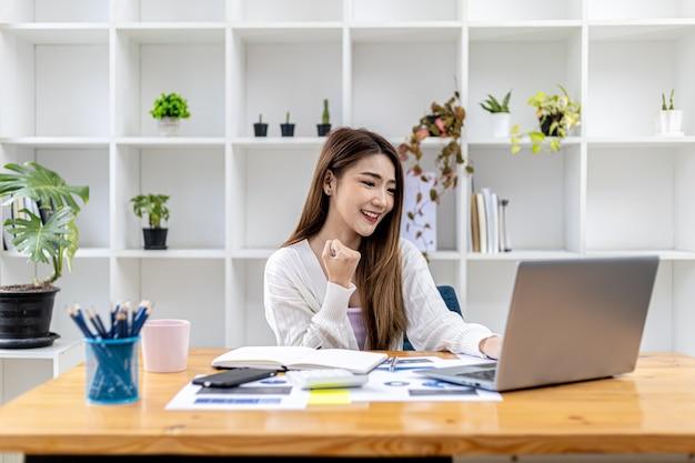 Schöne junge asiatische frau, die vor einem laptop, konzeptbild der asiatischen geschäftsfrau gestikuliert, die intelligente, moderne weibliche führungskraft, startgeschäftsfrau, geschäftsführerfrau arbeitet.