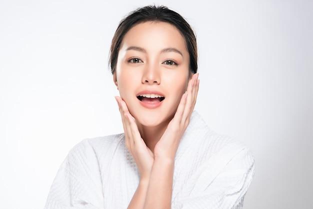 Schöne junge asiatische frau, die weiche backe und lächeln mit sauberer und frischer haut berührt. glück und fröhlich mit, isoliert auf weiss, schönheit und kosmetik,