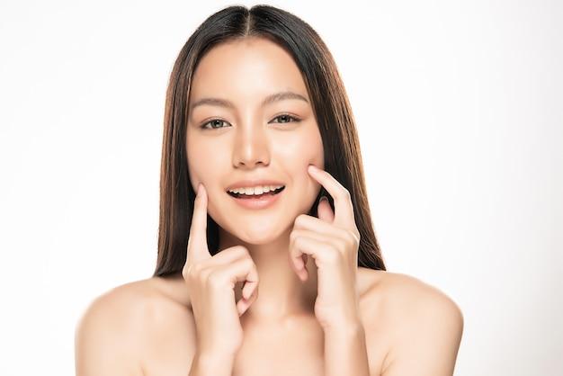 Schöne junge asiatische frau, die weiche backe und lächeln mit sauberer und frischer haut berührt. glück und fröhlich mit, isoliert auf weiße wand