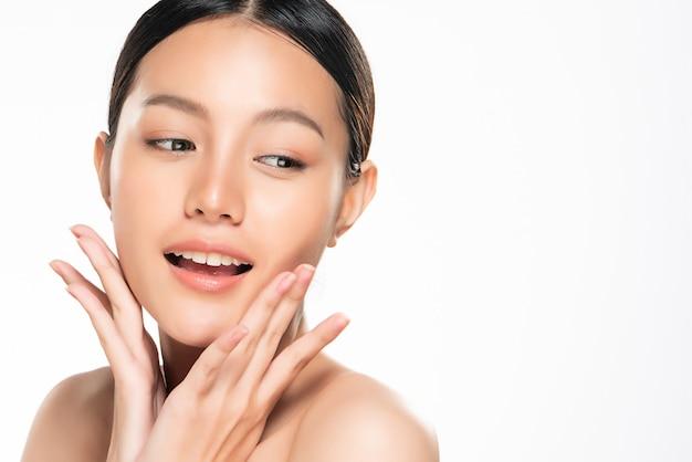 Schöne junge asiatische frau, die weiche backe und lächeln mit sauberer und frischer haut berührt. glück und fröhlich mit, isoliert, beauty and cosmetics concept,