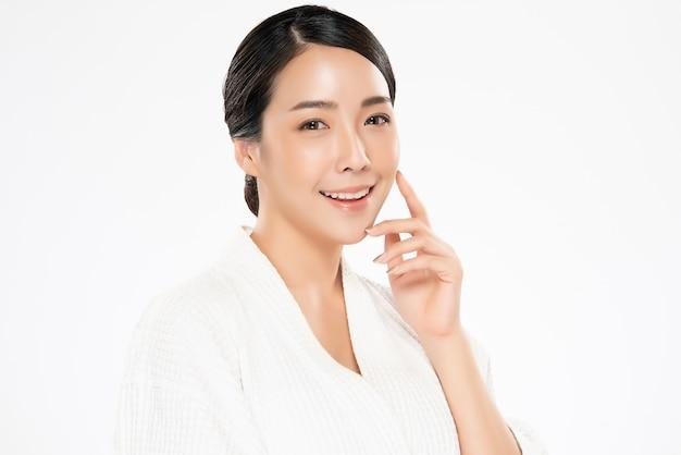 Schöne junge asiatische frau, die weiche backe und lächeln mit sauberer und frischer haut berührt. glücklich und fröhlich mit ,, beauty and cosmetics concept,