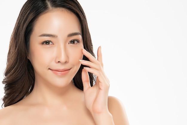 Schöne junge asiatische frau, die weiche backe und lächeln mit sauberer und frischer haut berührt