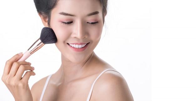 Schöne junge asiatische frau, die weiche bürste und kosmetik auf eigenem gesicht verwendet.