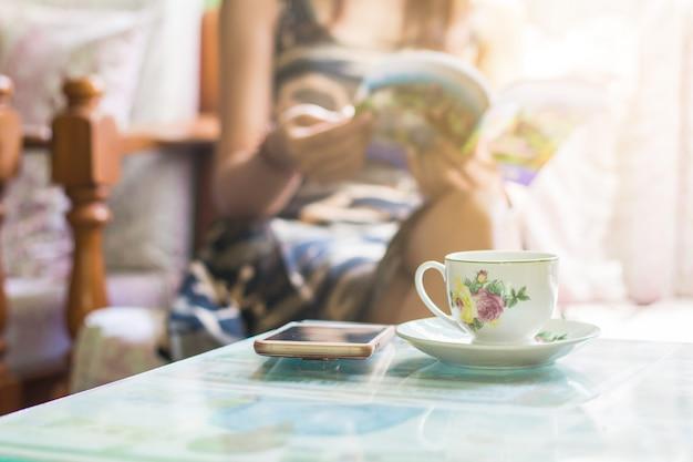 Schöne junge asiatische frau, die zu hause auf entspannender kaffeezeit des stuhls mit buch und smartphone sitzt