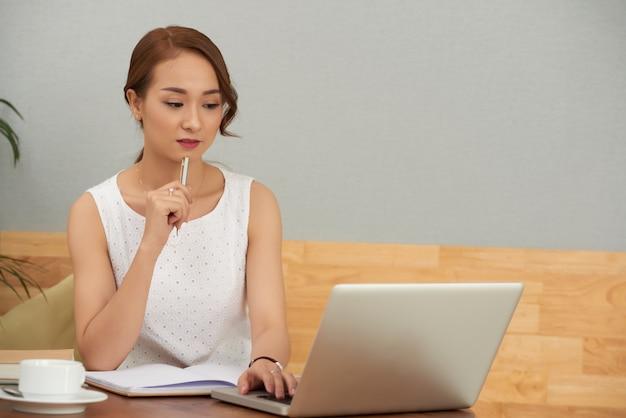 Schöne junge asiatische frau, die zu hause sitzt und an laptop arbeitet