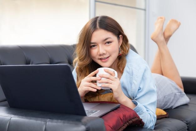 Schöne junge asiatische frau genießt ihre zeit zu hause, legt sich auf die couch, während sie ihren heißen kaffee hat und am computer arbeitet