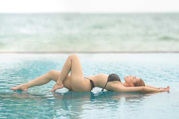 Schöne junge asiatische frau im bikini, der auf sandstrand entspannt, reist sommerferienkonzept im freien