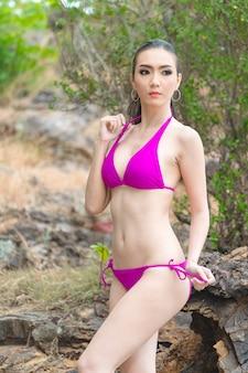 Schöne junge asiatische frau im bikini entspannend auf sandstrand, reisen sommerferienkonzept im freien