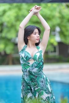 Schöne junge asiatische frau im bikinigrün entspannend auf sandstrand, reisen im freien sommerferienkonzept