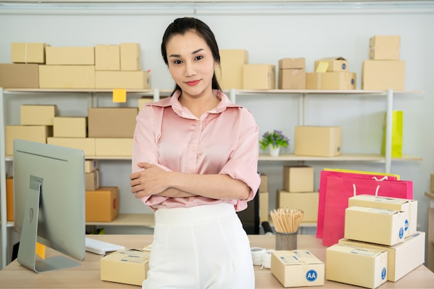 Schöne junge asiatische frau im elektronischen geschäftsverkehr und im on-line-einkaufen, glückliche frau, welche sich die gefälschte kreditkarte zeigt.