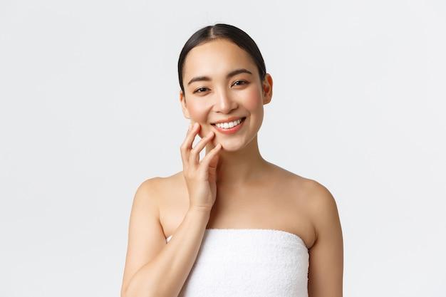 Schöne junge asiatische frau im handtuch, das im badezimmer steht, glücklich lächelt, saubere haut berührt, hautpflegeprodukte im badezimmer anwendet und sich um körper, weiße wand kümmert.