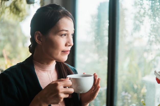 Schöne junge asiatische frau im trinkenden kaffee des cafés.
