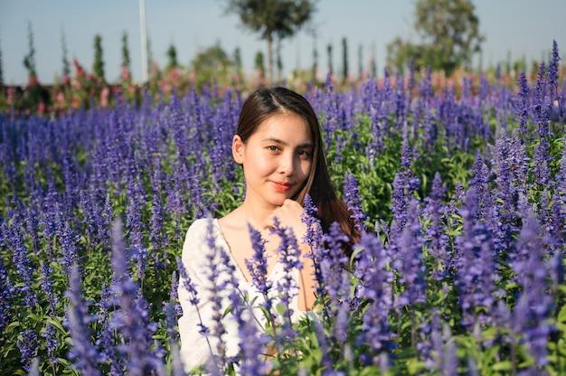 Schöne junge asiatische frau im weißen kleid, das im lavendelfeld auf sonnig genießt