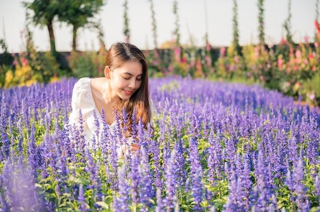 Schöne junge asiatische frau im weißen kleid, das lavendelblume im garten auf sonnig riecht
