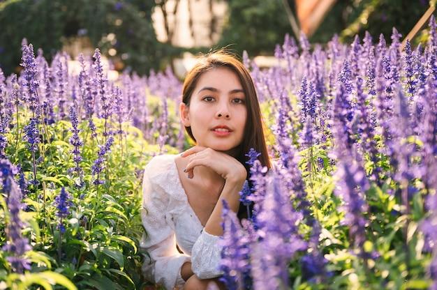 Schöne junge asiatische frau im weißen kleid, die im lavendelfeld auf sonnigem genießt